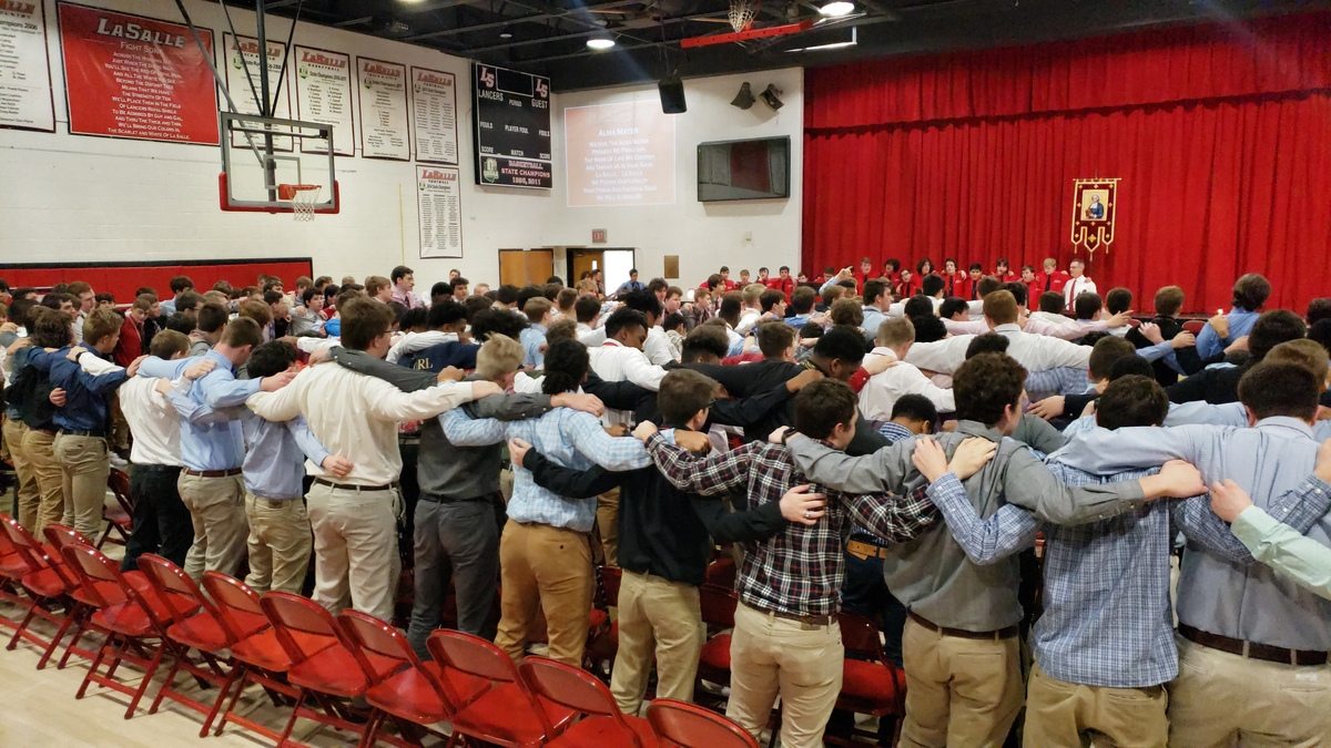 Students arm-in-arm in gym