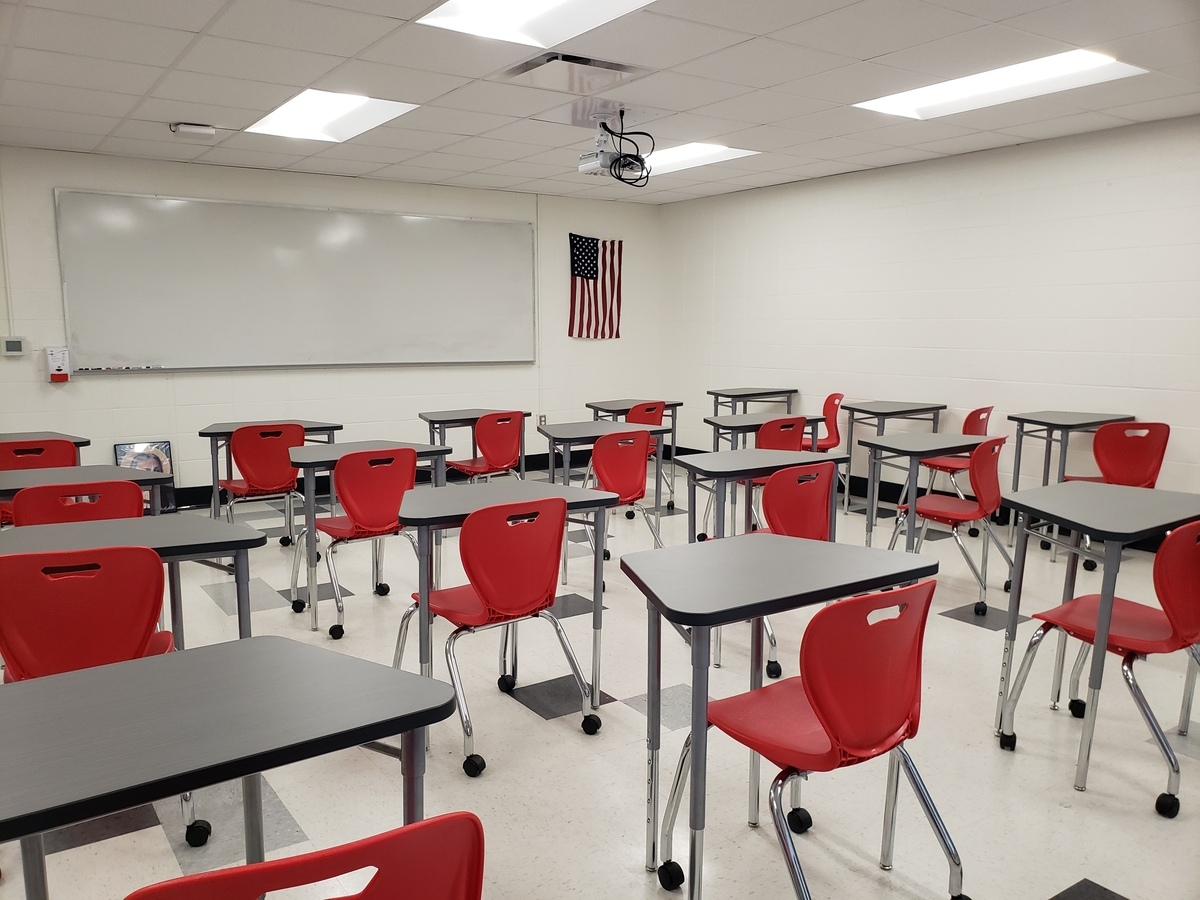 desks and red chairs in classroom