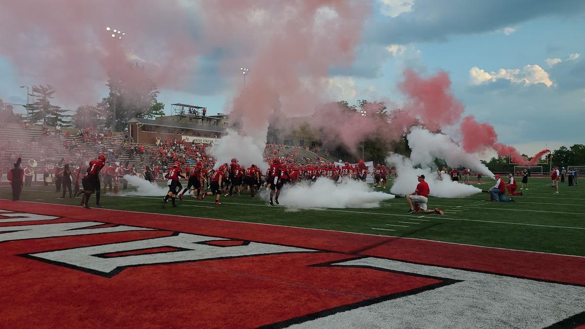 Football players walk through smoke on the field